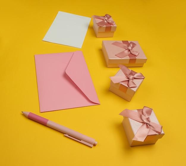 Koperta z listem i piórem, pudełka prezentów na żółtym tle. boże narodzenie, walentynki, urodziny.