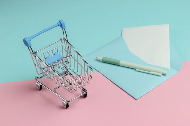 Koperta z listem i wózkiem na zakupy na różowym niebieskim tle pastelowych. makieta na walentynki, wesele lub urodziny.