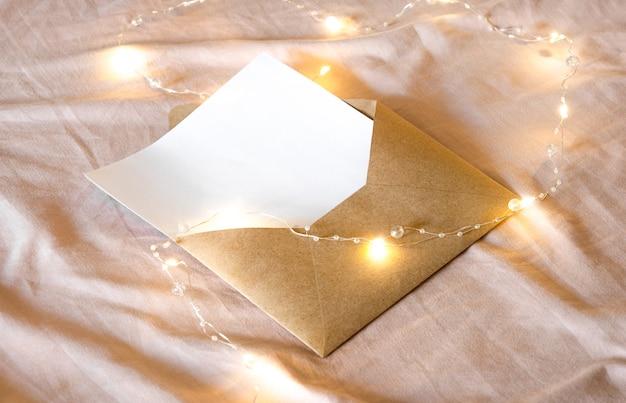 Koperta z listem leży na łóżku wraz ze świąteczną girlandą.