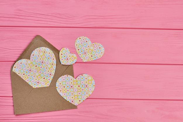 Koperta z papierowymi sercami, kopia przestrzeń. walentynki tło z kopertą rzemieślniczą i figurkami w kształcie serca na różowym drewnie.