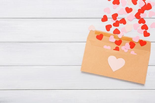 Koperta z papieru kraftowego z czerwonymi sercami rozłożonymi na białym drewnie