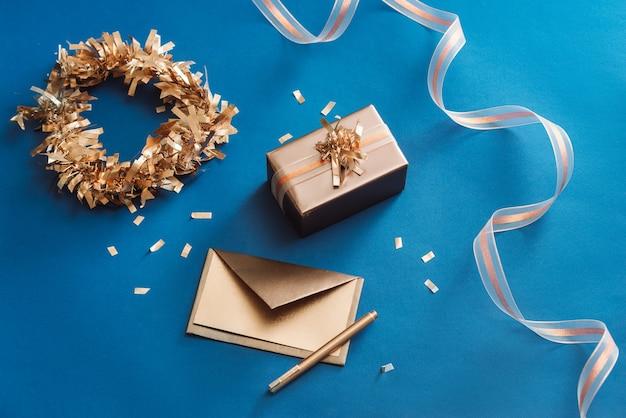 Koperta złota, pudełko, wstążka z wieńcem wykonana ze świątecznej dekoracji