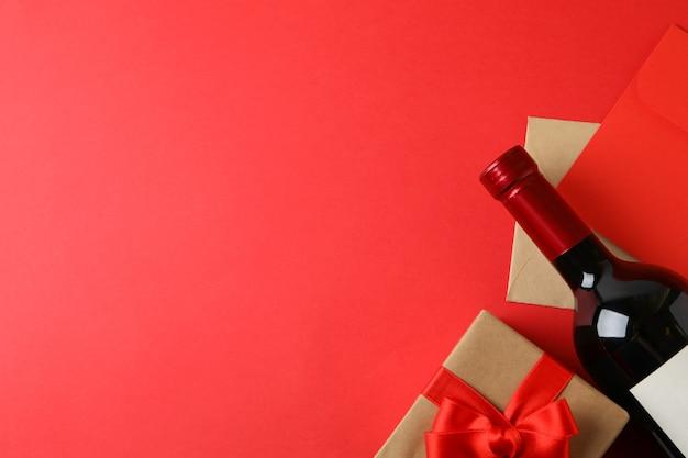 Koperty, pudełko i butelka wina na czerwonym tle
