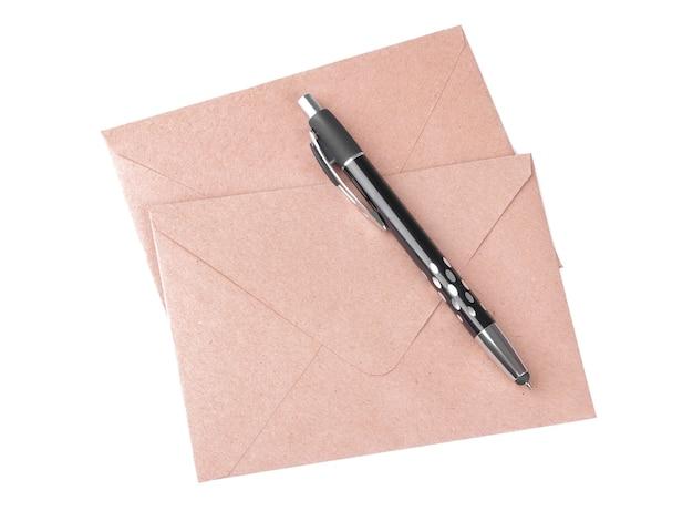 Koperty z papieru pakowego i długopis na białym tle na białym tle. poczta koncepcja widok z góry