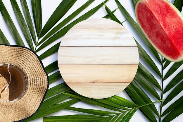 Kopia drewna z latem i arbuzem na tropikalnych liściach palmowych