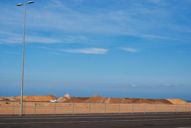 Kopiec czerwonego piasku na tle niebieskiego nieba w pobliżu drogi