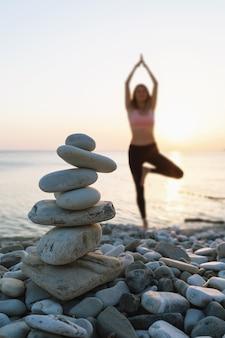 Kopiec kamieni na plaży na tle rozmytej kobiety wykonującej ćwiczenia vrikshasana