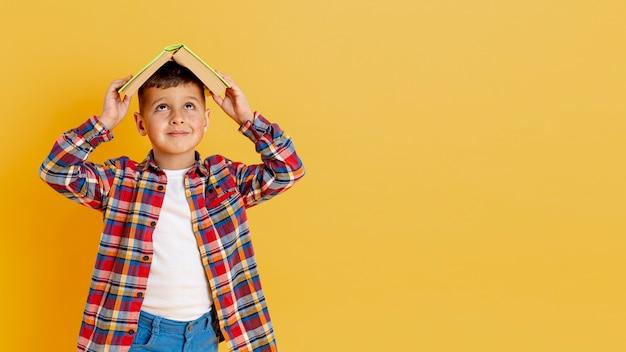 Kopiowanie miejsca chłopiec trzyma książkę na głowie