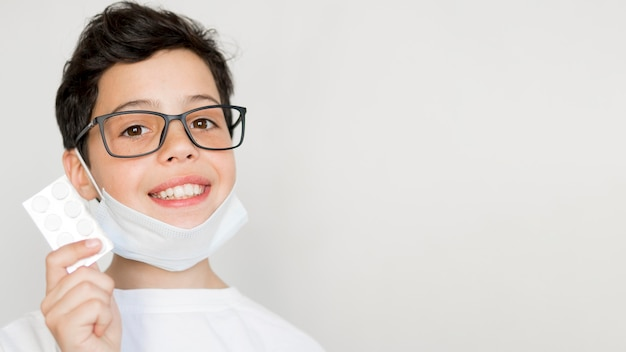 Kopiowanie miejsca chłopiec z maską trzymając tabletkę pigułki