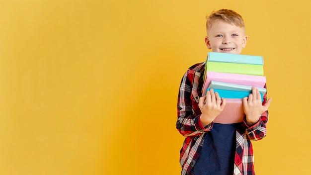 Kopiowanie miejsca mały chłopiec ze stosu książek