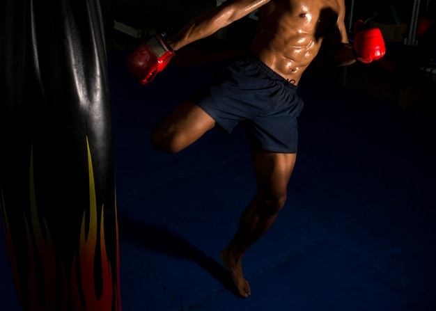Kopnięcie boksera na cel na ringu bokserskim w siłowni