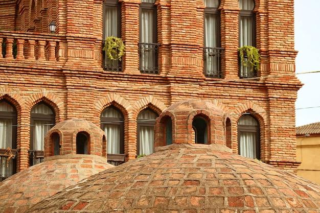 Kopuła średniowiecznych łaźni siarkowych ze starymi budynkami w tle stara gruzja tbilisi