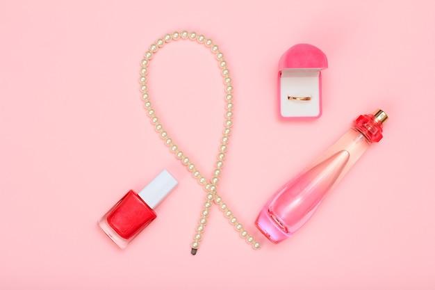 Koraliki, butelka perfum, lakier do paznokci i złoty pierścionek w pudełku na różowym tle. perfumy, kosmetyki i akcesoria dla kobiet. widok z góry.
