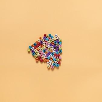 Koraliki w kształcie litery hobby wielu ludzi jest ułożone na żółtym tle, ułożone razem.