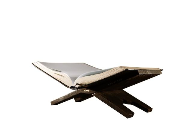 Koran otwarty na drewnianej podkładce na białym tle
