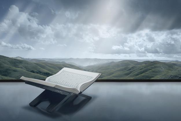 Koran otwarty w drewnianej podkładce z tłem z widokiem na góry