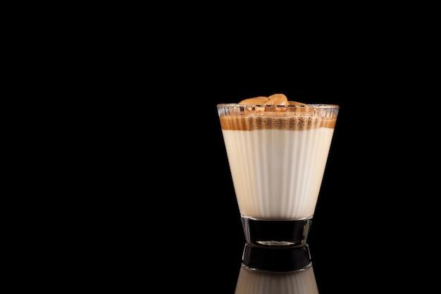 Koreańczyk pije kawę dalgona w pięknym kieliszku. zimne mleko z pianką z kawy rozpuszczalnej.