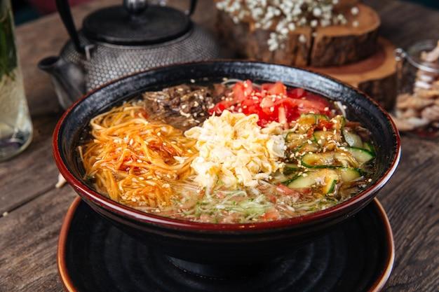 Koreański danie z makaronem kuksi z wołowiną i warzywami