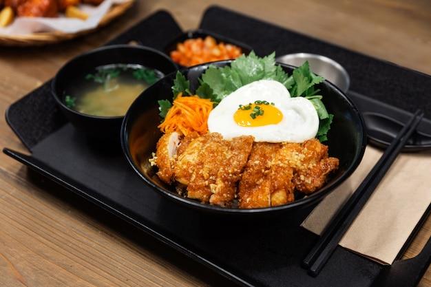 Koreański kurczak głęboko smażony z czosnkiem z ryżem i jajkiem sadzonym