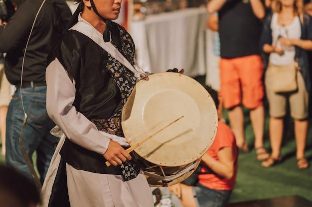 Koreański ludowy mężczyzna wykonuje z tradycyjnym instrumentem plenerowym