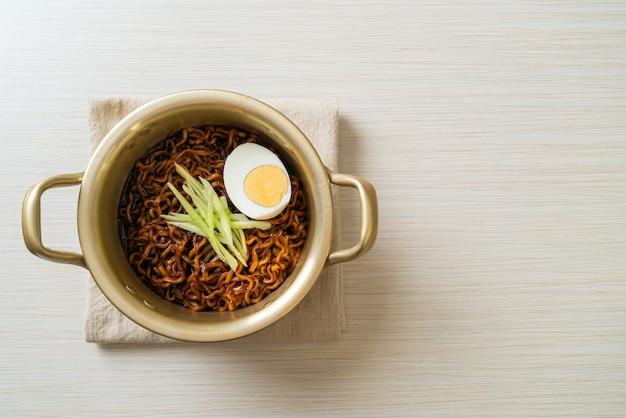 Koreański makaron błyskawiczny z sosem z czarnej fasoli pokryty ogórkiem i jajkiem na twardo (jajangmyeon lub jjajangmyeon) - po koreańsku