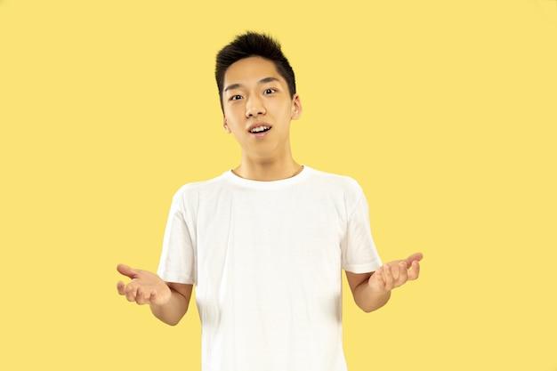 Koreański młody mężczyzna w połowie długości portret na żółtej ścianie