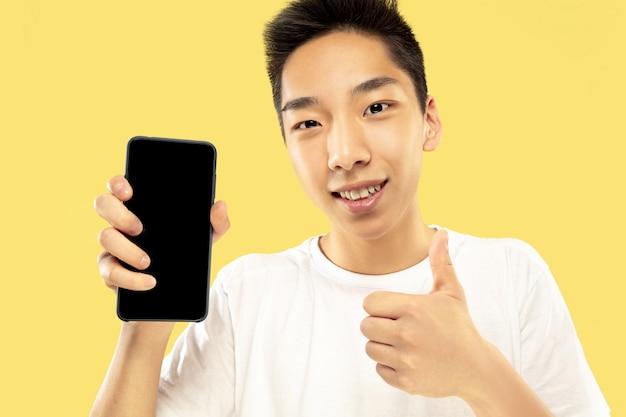 Koreański młody mężczyzna w połowie długości portret na żółtym tle studio. model męski w białej koszuli. używanie smartfona do obstawiania, czytania wiadomości lub rozmów. pojęcie ludzkich emocji, wyraz twarzy.