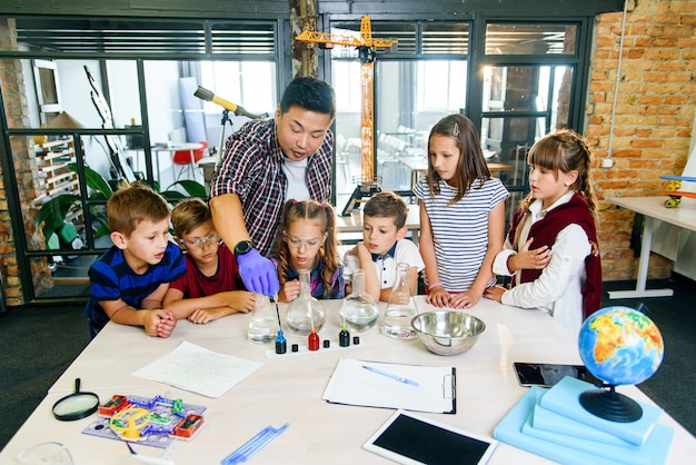 Koreański naukowiec pokazuje uczniom szkół podstawowych eksperymenty dotyczące reakcji chemicznych w nowoczesnej klasie laboratoryjnej.