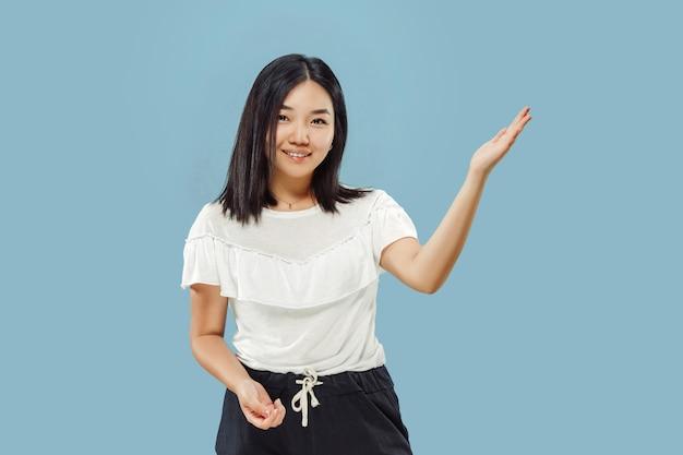 Koreański portret młodej kobiety w połowie długości. modelka w białej koszuli. pokazuje i wskazuje coś. pojęcie ludzkich emocji, wyraz twarzy. przedni widok.