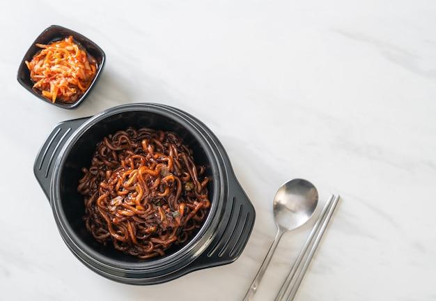 Koreańskie czarne spaghetti lub makaron instant z pieczonym sosem sojowym chajung (chapagetti). koreański styl jedzenia