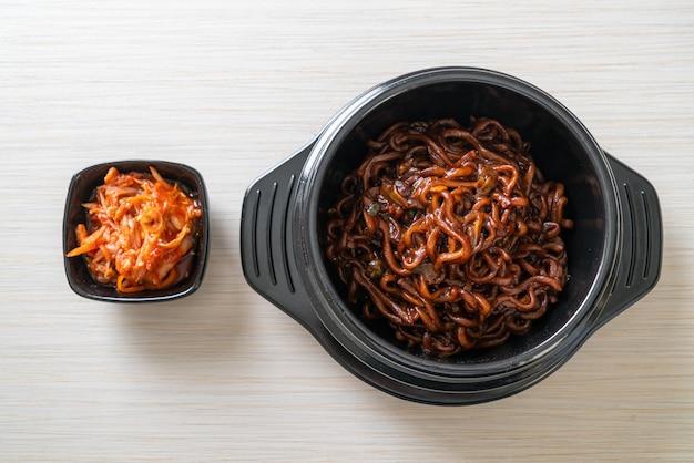 Koreańskie czarne spaghetti lub makaron instant z pieczonym sosem sojowym chajung (chapagetti), po koreańsku