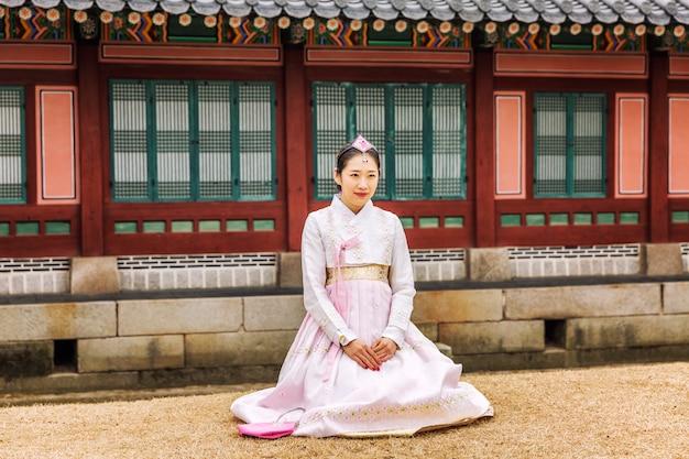 Koreańskie dziewczyny w hanboksach idą przez piękny park.