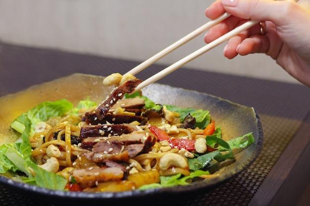 Koreańskie jedzenie. dziewczyna zjada pałeczkami koreańskie danie z mięsa, orzechów i warzyw.