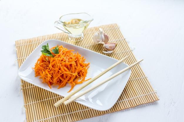Koreańskie marchewki na białym drewnianym stole