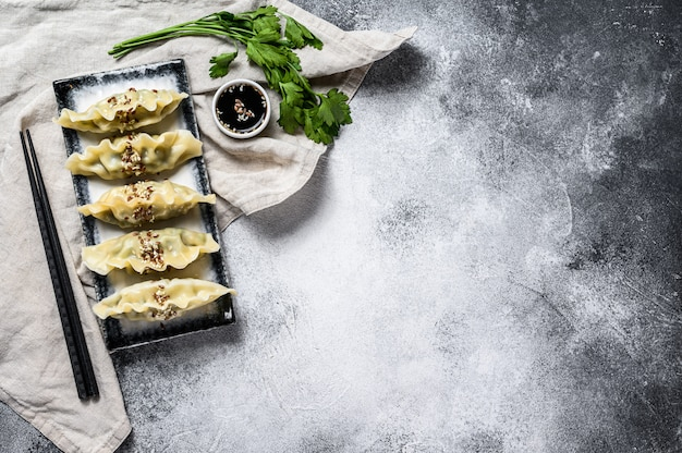 Koreańskie pierożki gotować na parze na talerzu ceramicznym. szare tło. widok z góry. miejsce na tekst.