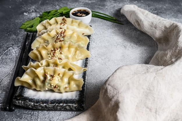 Koreańskie pierożki gotować na parze na talerzu ceramicznym.
