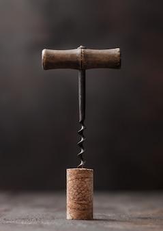 Korek do wina z rocznika korkociąg na górze na tle drewniany stół.