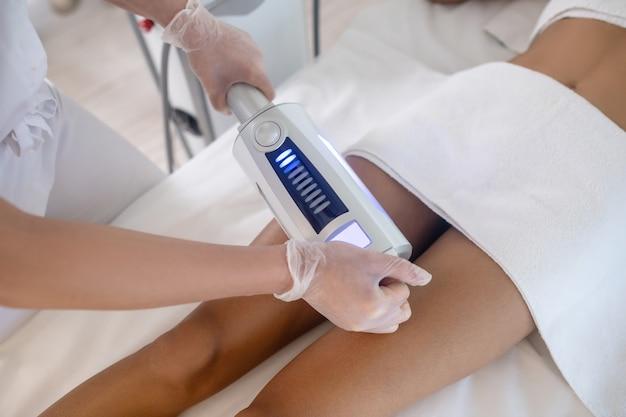 Korekta ciała. ręce lekarza z aparatem roboczym do korekcji ciała na nodze leżącego pacjenta w centrum medycznym