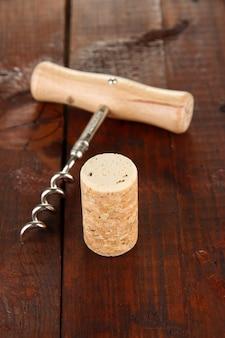 Korkociąg z korkami do wina na drewnianym stole, widok z góry