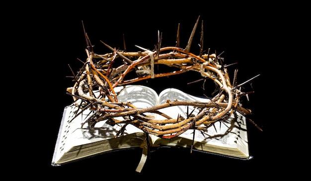 Korona cierniowa leży w księdze biblijnej w ciemności. pojęcie wielkiego tygodnia i ukrzyżowania jezusa.