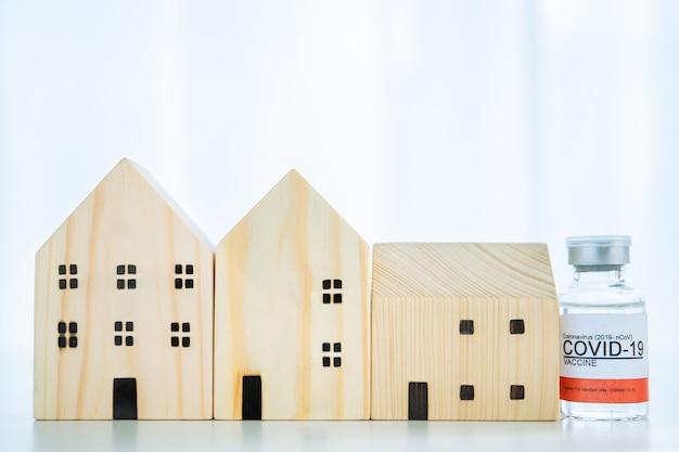 Koronawirus, 2019-ncov lub covid-19 szczepionka i strzykawka do wstrzykiwań z drewnianym modelem domu, koncepcja opieki zdrowotnej i ochrony rodziny przed covid-19 z copyspace.