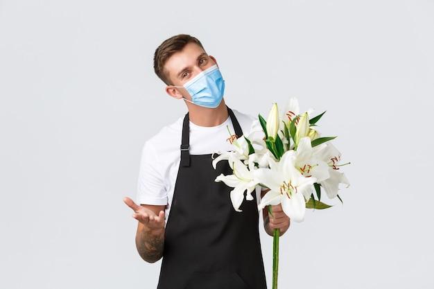 Koronawirus, biznes dystansowania społecznego podczas koncepcji pandemii covid-19. uroczy sprzedawca, kwiaciarnia w kwiaciarni robi bukiet białych lilii dla klienta, noszący maskę medyczną