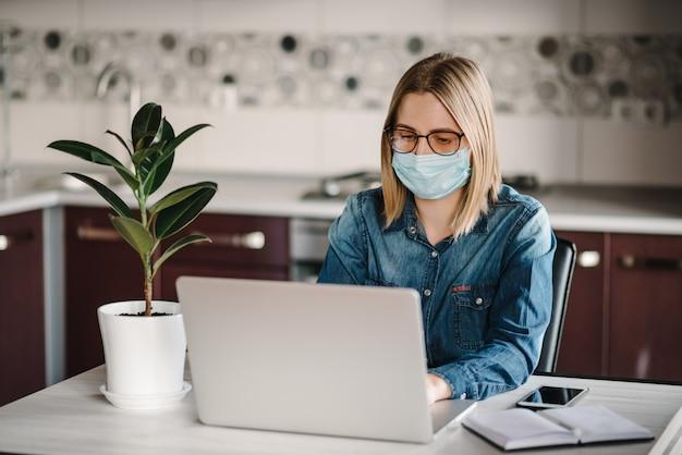 Koronawirus. biznesowa kobieta pracuje w domu, będący ubranym maskę ochronną w kwarantannie.