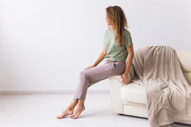 Koronawirus, covid-19, kwarantanna, izolacja, świat pandemiczny koronawirusa. zostań w domu. znudzona kobieta spędza czas siedząc na kanapie w domu.