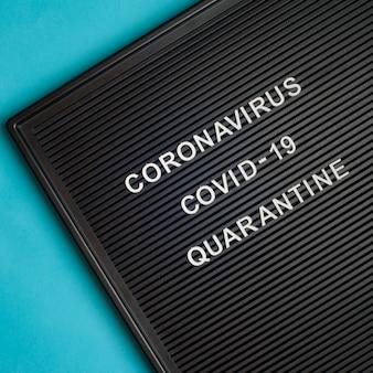 Koronawirus - covid -19 - kwarantanna - tekst na czarnej tablicy na niebieskim tle.
