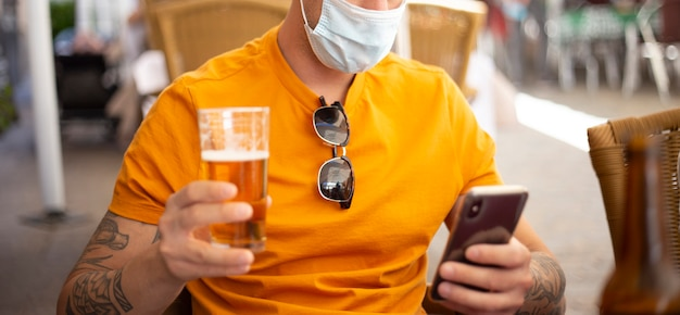 Koronawirus. człowiek z piwem, ubrany w maskę ochronną. dystans społeczny. pij bezpieczeństwo.