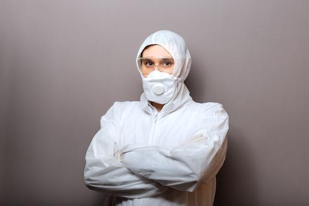 Koronawirus, dezynfekcja covid-19. portret lekarza w ochronnym kombinezonie medycznym, zagrożenie biologiczne, gogle maski medycznej na białym tle na szarym tle.