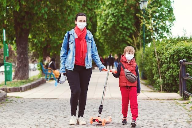 Koronawirus epidemia. matka i syn na spacerze podczas kwarantanny coornavirus. zapobieganie koronawirusowi.