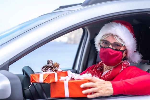 Koronawirus i czas bożego narodzenia. starsza kobieta w czapce mikołaja i masce medycznej, aby uniknąć zakażenia koronawirusem, jeździ samochodem, by dostarczyć do domu prezenty świąteczne.