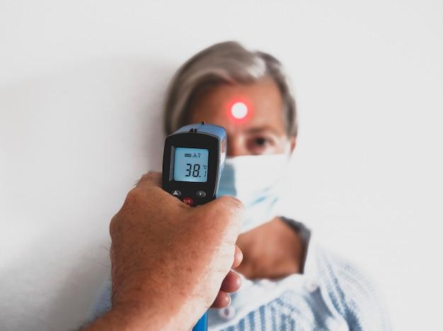 Koronawirus infekcja. kontrola temperatury starszej kobiety noszącej maskę medyczną – emeryci z maską, aby uniknąć zakażenia koronawirusem covid-19. koncepcja zapobiegania i leczenia